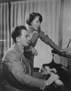 At home, Clifford Odets plays the piano while his wife Luise Rainer looks on