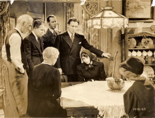 From left: Clem Bevans, Regis Toomey, Janet Beecher (back to camera), Irving Bacon, Spencer Tracy, Luise Rainer, [??] in a scene from Big City (1937)